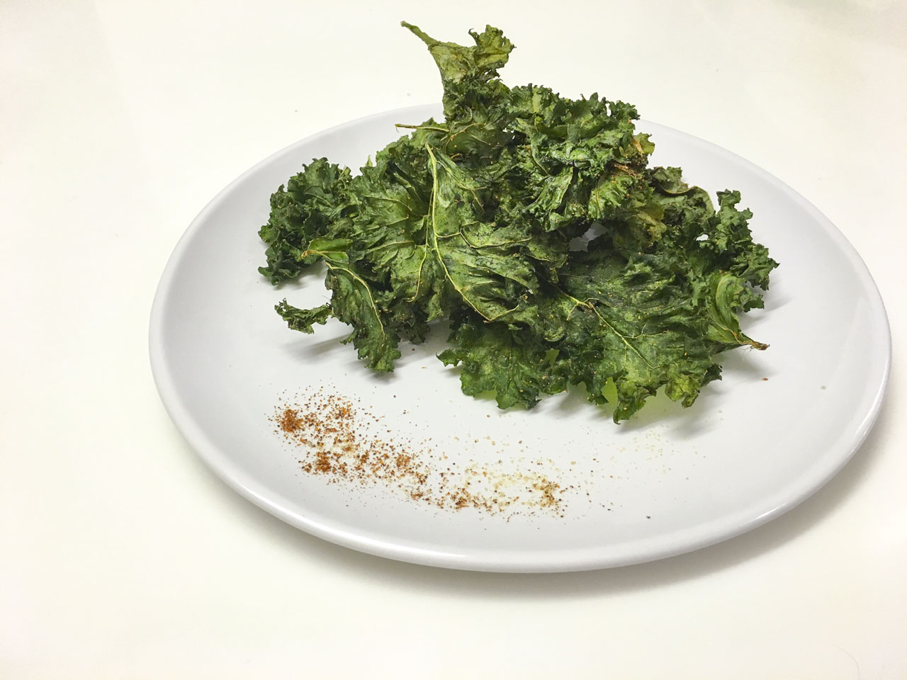 Kale chips seasoned with chili spice on a plate