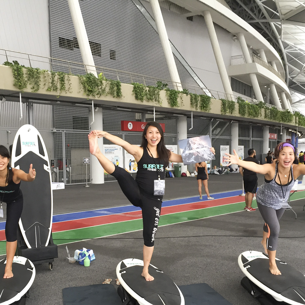 Instructors in yoga poses on surfset board during sweatfornepal